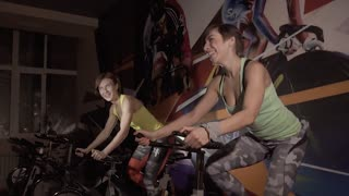 Two happy young fitness women training on exercise bikes together at night