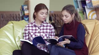 Two interested female students discussing articles from magazine