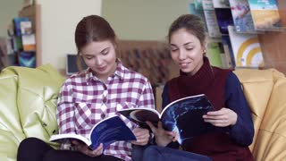 Two smiling female students having good time in library