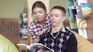 Two young friendly students looking through a book together