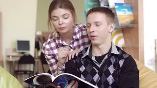 University boy discussing an article from a book with pretty university girl