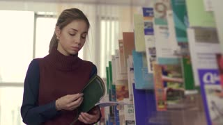 University girl thumbing through a book while standing near the bookcase