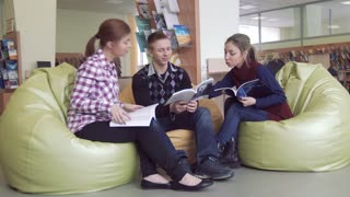 University students in library discussing articles from their books