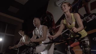 Young people at the gym exercising on stationary bikes at night