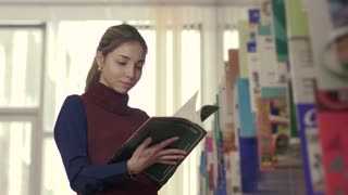 Young woman in a library reading a chosen book