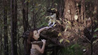 Wild-looking girl standing under the tree holding a wolf is paw