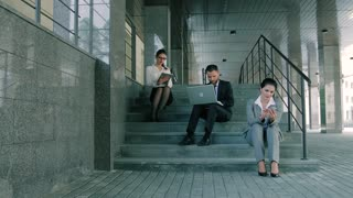 Young and attractive business people working on stairs using laptop, tablet and smartphone