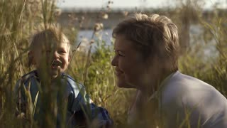 Young attractive mother having fun with her son in beautiful field near the river