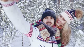 Young attractive woman and young smiling man taking beautiful photo in winter forest
