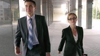 Young businessman accompanies an attractive delegate to the office building