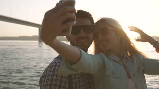 Young couple in love taking selfie together after wonderful day on beach