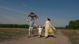 Young family of three people having fun with their son. They run and fly a colorful kite
