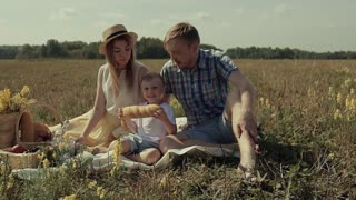 Young family sitting in the meadow and having family picnic