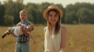 Young family spending time in nature. Woman smiling on the camera. Father rotating his son in arms