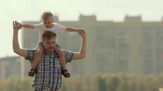 Young father holding his son on the shoulders rotates around. Mother walking in to kiss her little son