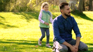 Young father sitting on green grass and smiling little girl runs up to him and puts her hands to his eyes