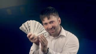 Young happy man waving a fan of dollars