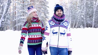 Young loving couple wearing bright winter clothes walking in the snowbound forest