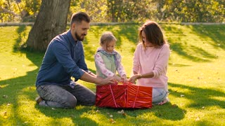 Young loving family trying to undo the ribbon of birthday present