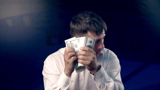 Young man looks back while counting a big amount of money
