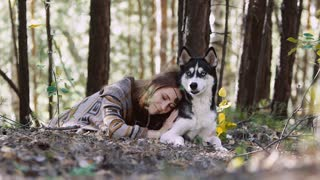 Young natural woman lying on a meadow and hugging her wolf-looking dog