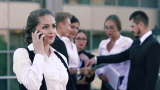 Young smiling business woman discussing her successful working day on the phone and her colleagues chatting in the background