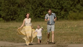 Young smiling family of three people running down the countryside road with a kite