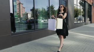 Young woman in little black dress spins around on the street. Slow motion