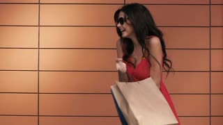 Young woman in red dress laughing enjoying her shopping. Slow motion