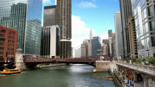 A time lapse of the Chicago River, surrounded by skyscrapers, with boats passing by