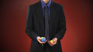 An anonymous businessman in a suit juggles 3 balls in front of a red background.