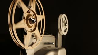 Close-up on the spinning film reels of an antique 8mm film projector in a dark room. Includes projector audio