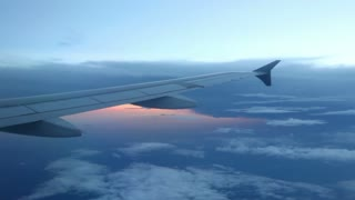Looking out a jet window at a blue cloudscape with the sunset reflecting off water in the distance