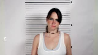 Police mug shots of a female criminal holding a placard, standing in front of a white rulered wall.