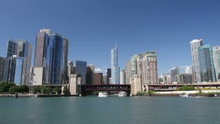 Smooth moving shot of the Chicago skyline from the water, with boats entering and exiting the Chicago River