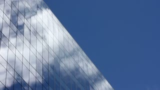Time lapse, looking up at a glass-covered skyscraper, reflecting the blue sky and passing clouds