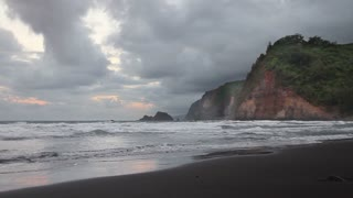 Time lapse of a Hawaiian coastline with cliffs and a rare black sand beach on a cloudy day
