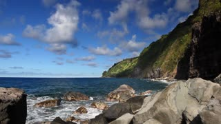 Time lapse of a rocky coastline line with steep foliage-covered cliffs in Hawaii, clouds rolling by overhead