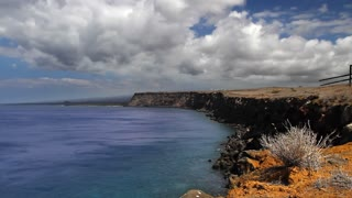 Time lapse of the coastline of the southernmost point in the USA, lined with steep cliffs dropping off into the blue pacific ocean