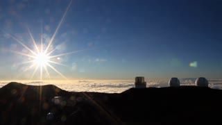 Time lapse of the telescopes on the summit of Mauna Kea in Hawaii, above the clouds as the sun sets