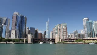 Time lapse shot with a smooth motion view from a boat as it enters the mouth of the Chicago River, passing under bridges and through skyscrapers into the center of Chicago