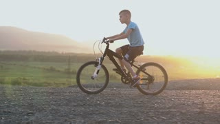 8-9 year boy in blue T-shirt who rides a black bike in a mountainous place at the summer in the sunset or in the sunrise. The child riding his bicycle on the stone road above the river, slow motion