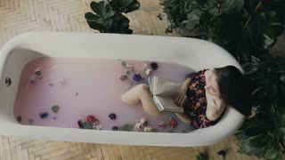 A beautiful girl reads a book and relaxing in a warm bath filled with milk and fragrant flower buds. Young woman read interesting book in bath, 4k