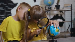 A beautiful girl with a boy through the magnifying glass looks at the globe in the classroom. On a geography lesson, children study the globe. Traveling around the world, slow m
