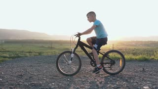 A beautiful little boy who rides a black bike in a mountainous place in the summer in the east or in the sun. The child is cycling on top of a mountain over the river, slow motion