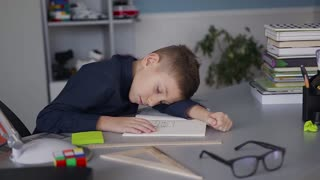 A beautiful schoolboy fell asleep on the table when doing homework. The guy is dressed in a blue shirt. On the desk books and notebooks slow motion