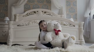 A charming girl sits on the floor at the bedside and joyfully plays with soft teddy bear. Cheerful baby and her teddy bear is a soft, white toy slow motion