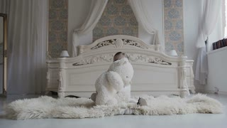 A charming girl sits on the floor at the bedside and joyfully plays with soft teddy bear. Cheerful baby and her teddy bear is a soft, white toy. White bedroom