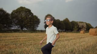 A child in the field. A boy in his glasses looks at the sunset slow motion