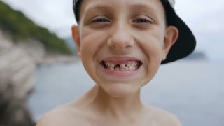 A cute toothless boy in cap is smiling on the camera at sea background. Portrait of a smile schoolboy without teeth, slow motion